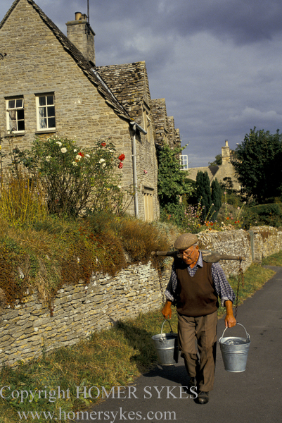 MAN COLLECTS DRINKING WATER FROM VILLAGE RIVER STREAM ENGLAND 1980S