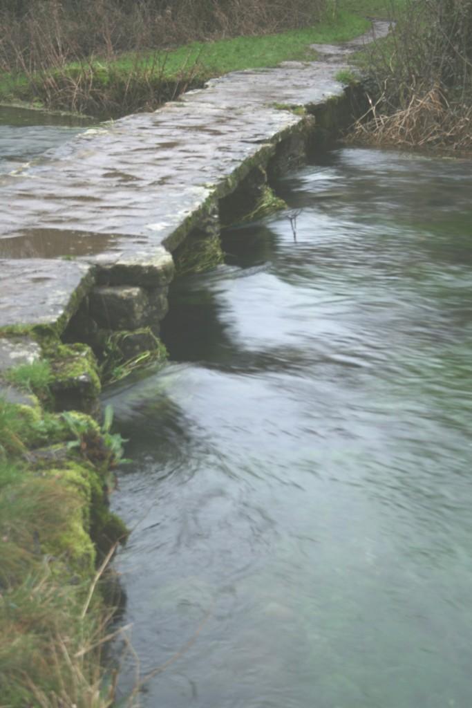 The River Leach floods under the clapper bridge - Eastleach